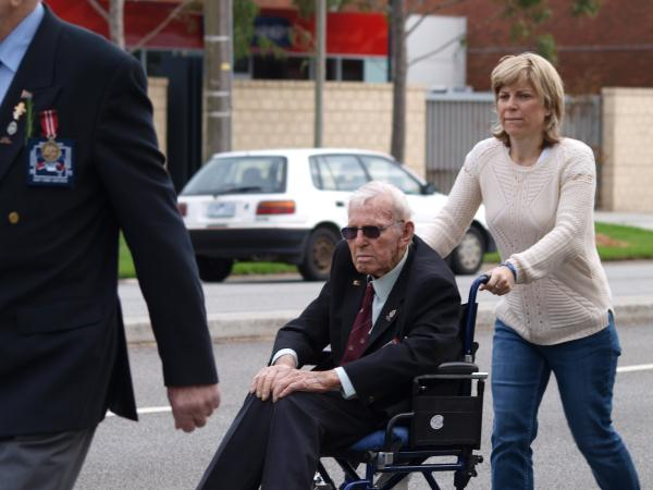 World War II veteran Geoffrey Charters and daughter Carol march down Springvale Road.