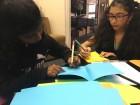 Saki and Tara work on cards for stallholders.